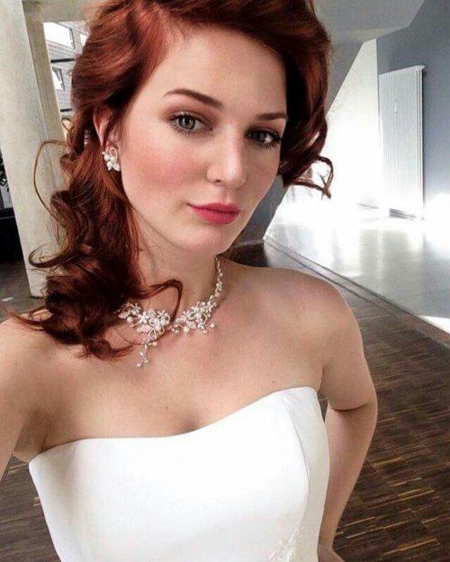 Rothaarige, junge Frau in weißer Korsage & Perlenhalsreif bei Fotoshooting mit Make-up, im Hintergrund Holzfußboden & lichtdurchfluteter Raum