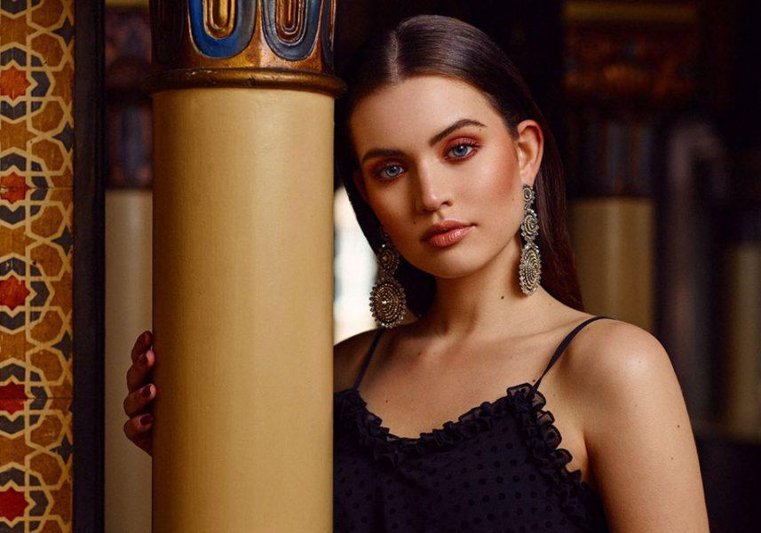 Brünette Frau lehnt Stirn an orientalische Säule, trägt Spaghetti Top, opulente Ohrringe & Oriental Make-up