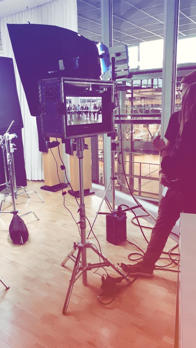 Aus Sicht eines Visagist Hair & Make-up Artist für Werbefilm: Display in Box mit Foto Gruppe von Menschen an Tisch. Stative, Spots, Softboxen & halb angeschnitten zwei Menschen im rechten Bildrand, große Fenster & Vorhang im Hintergrund