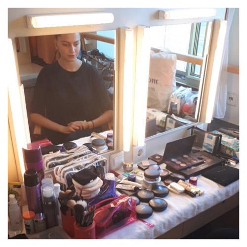 Spiegel mit vielen Make-up Utensilien, Frau sitzt davor bei Event Make-up und Hairstyling