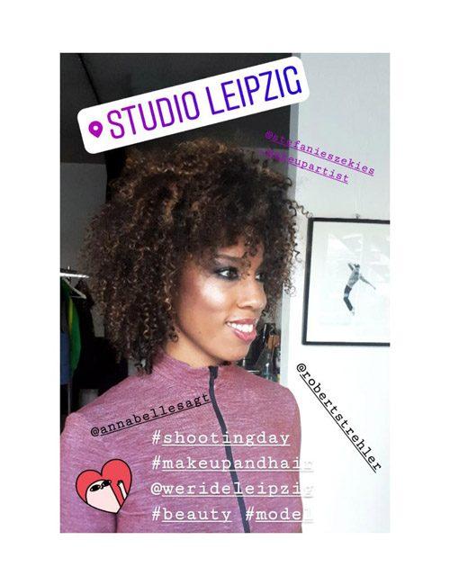 Schnappschuss in Fotostudio eines dunkelhäutigen Models mit Curls, lila Zipper & glänzendem Make-up für Editorial-Shooting