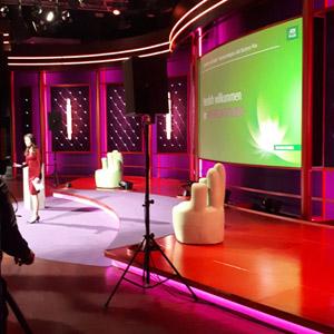 Bühne in rot/rosa mit zwei Sesseln, grünem Screen, Lautsprecher auf Ständer, Moderatorin im linken Hintergrund mit Event Make-up Look