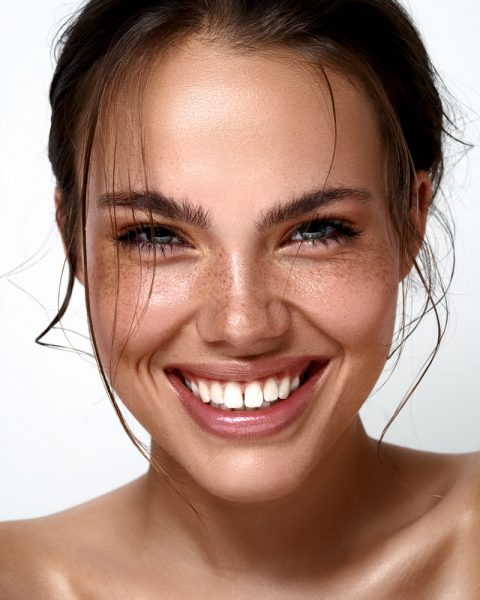 offen lachende Frau mit strahlend weißen Zähnen, verspielte Haarsträhnen im Gesicht, tolles Hair & Make up