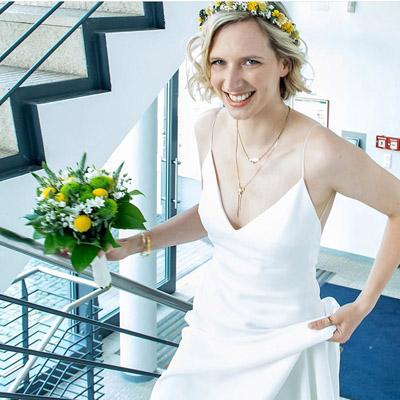 Junge Braut geht Treppen hoch, trägt Blumen & Hairstyles for short hair