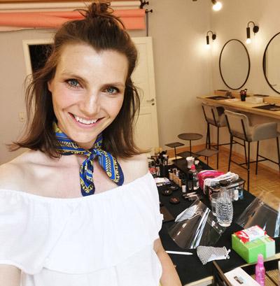 Selfie einer Visagistin bei einer Make-up Artist Schulung vor Make-Up Utensilien & Schminktischen