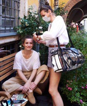 Visagistin mit Maske & Tasche, stylt Model bei Fotoshooting mit Make-up auf Bank, Hinterhof, Blumen