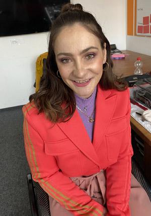 Kristina Vogel, brünette junge Frau in roter Jacke sitzt auf Stuhl mit Make-up für TV Sendung