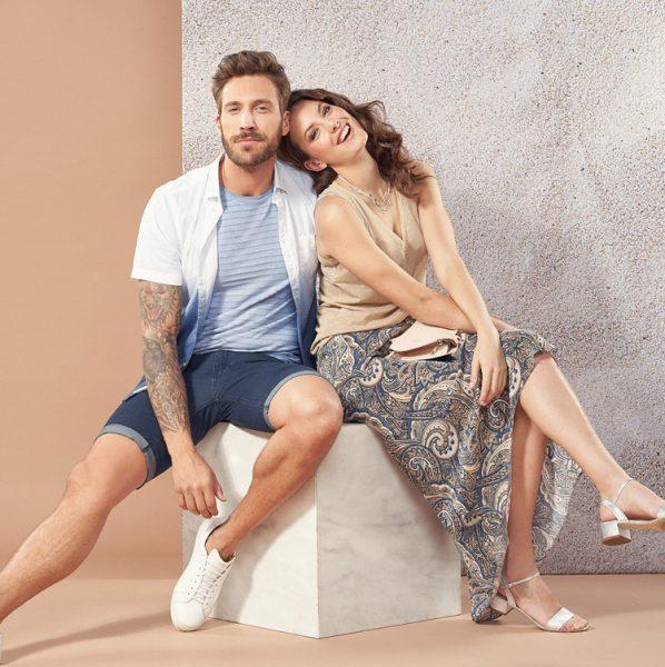 Junges Paar sitzt auf Kubus in sommerlichen Outfits, gestylt mit Fotoshooting Make-up