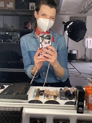 Selfie einer Make-up Artistin mit Maske, Make-up Utensilien, im Hintergrund Fotoshooting