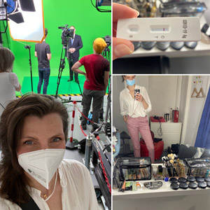 Selfie einer Frau in Fotostudio mit Green Screen und Personen im Hintergrund. Covid-Test, Make-Up Utensilien für Shooting