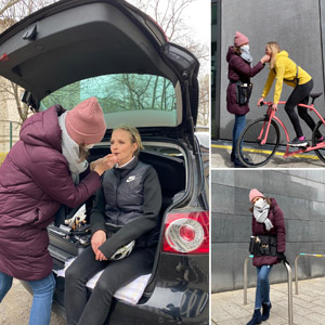 Frau schminkt Model im Kofferraum eines Autos für Fotoshooting Make-up. Frau auf Fahrrad, Frau lehnt an Fahrradständer